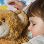 bambino con peluche che dorme su un materasso per bambini